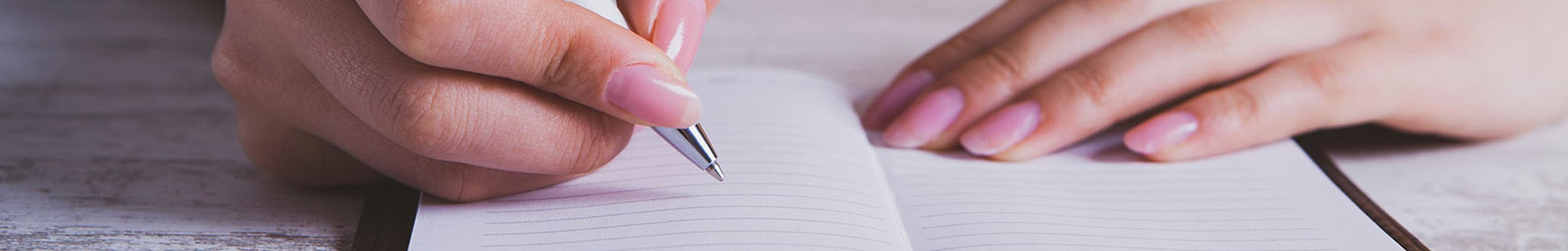 Woman writing in a lined notepad