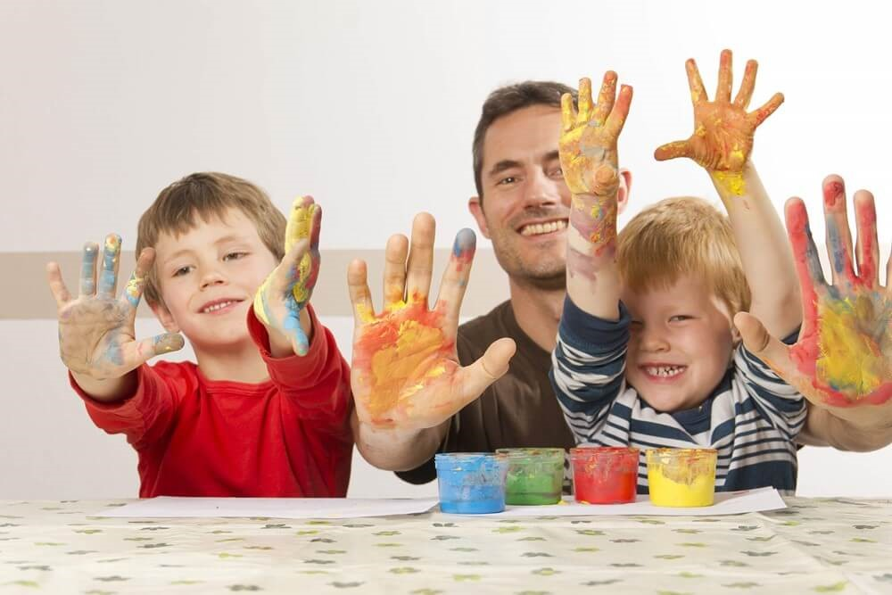 Children and father with paint on hands